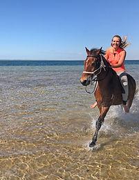 A girl cantering on a bay horse through the sea in Mozambique.