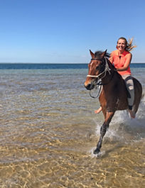 A girl cantering on a bay horse through the sea in Mozambique.