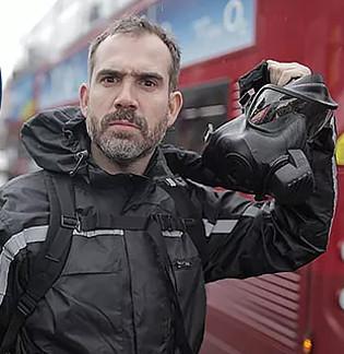 Dr. Xand Van Tulleken holding a gas mask