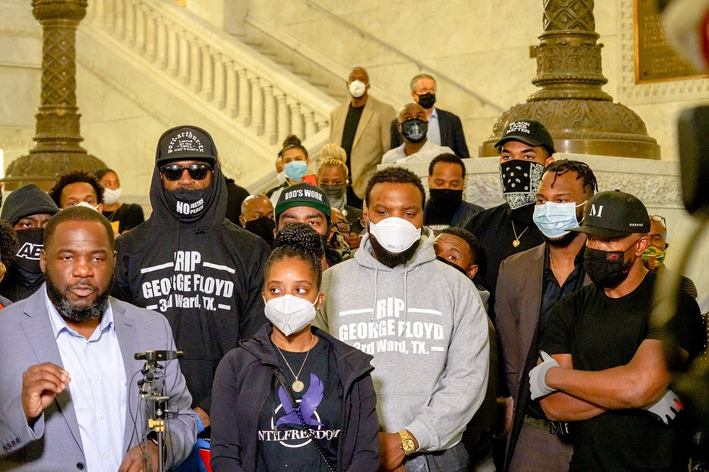 """Upon the death of George Floyd, his long-time friend and former NBA player, Stephen Jackson, seen with sunglasses and a black hoodie attends a protest in Minneapolis. He was accompanied by other NBA players and star center, Karl Anthony-Towns (back right). Stephen Jackson also mentioned the bond between him and George Floyd: """"Every city, every team I played on everywhere I was, we talked. He was excited with everything I did""""."""