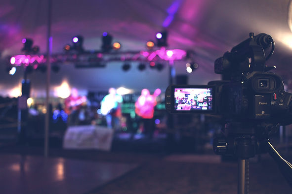 Canon camera pointing at a band shooting video of a live concert