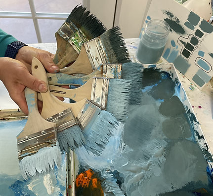 Lucy Liew holding 8 industrial flat brushes dipped in different shades of blue gray paint