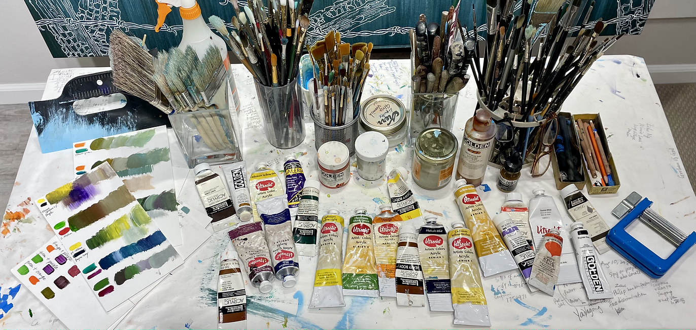 High angle shot of table covered with acrylic paint tubes, paintbrushes, and paint swatches
