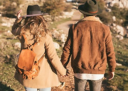 back-view-man-woman-holding-hands-outsid