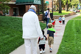 Children are accompanied by elders and staff on a morning walk to the park.