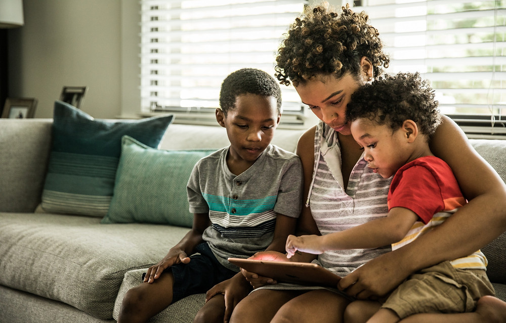 A woman with two young children sitting on a couch and engaging with a tablet
