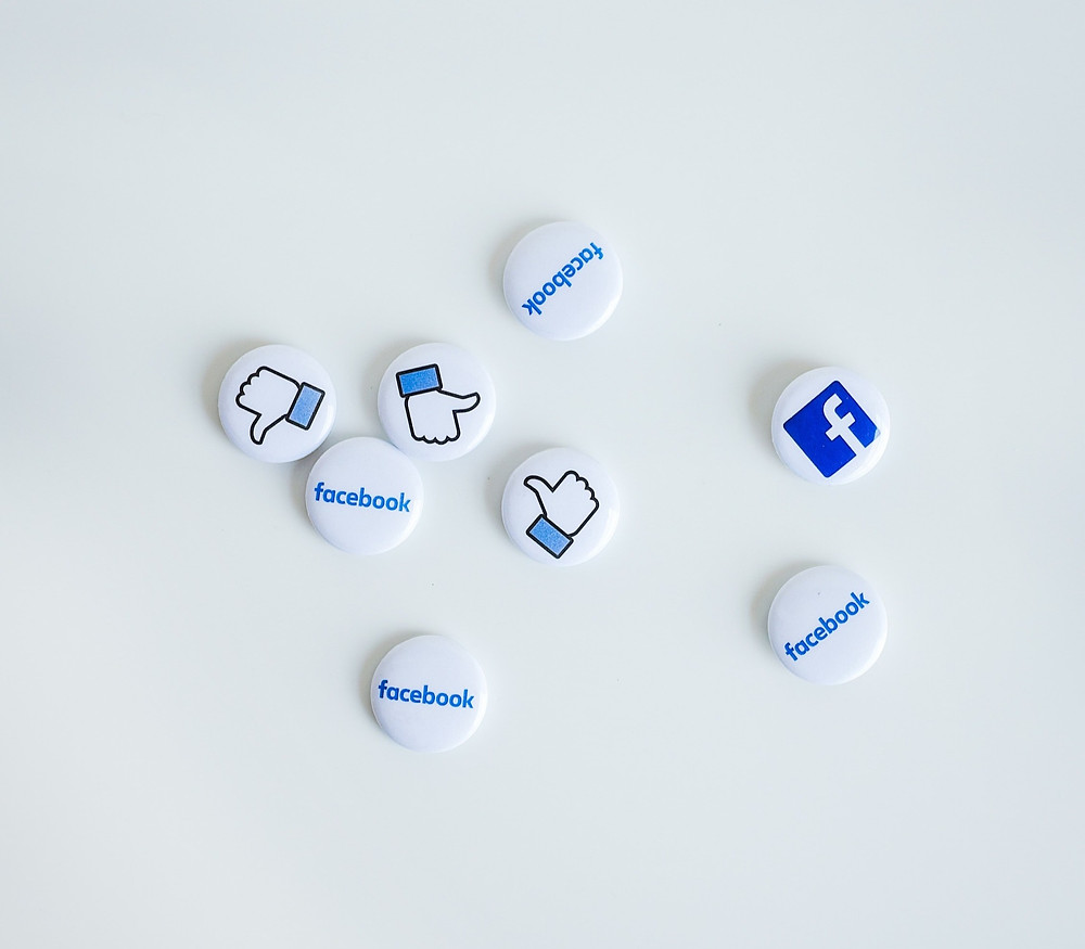 White badges with Facebook symbols on them