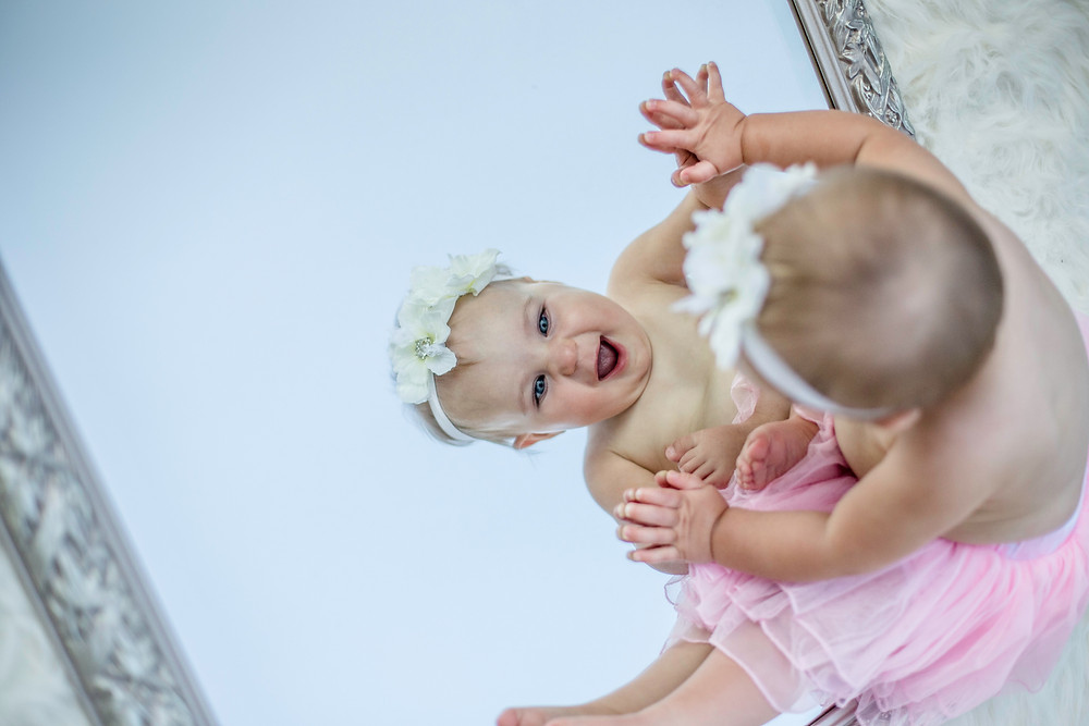 A smiling baby girl dressed in a pink tutu and a flowery head-band, looking at her reflection in the mirror absolutely delighted