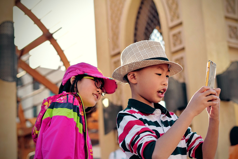 Two children at an amusement park engaging with a smartphone