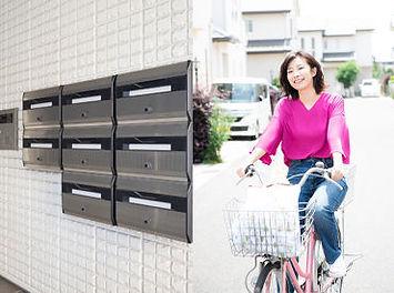 自転車に乗ってポスティングをする女性