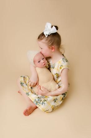 Newborn & girl sibling in yellow
