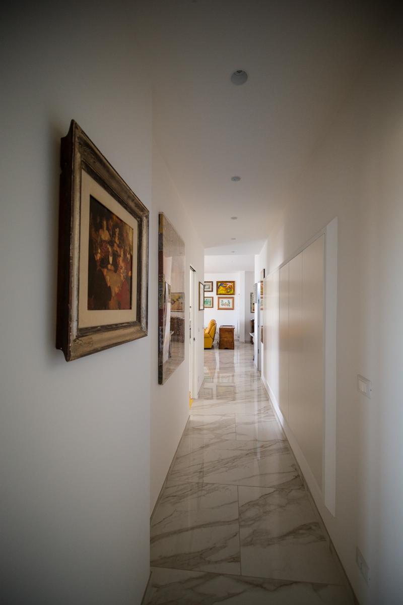 corridoio con scarpiera e quadri