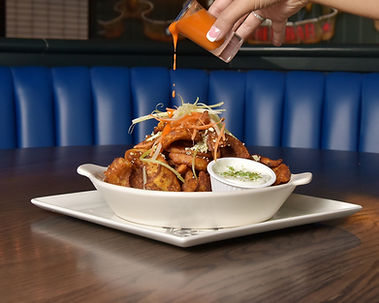 KSNI Food Photography Buffalo sauce being drizzled on to chicken wings in a booth in a restaurant
