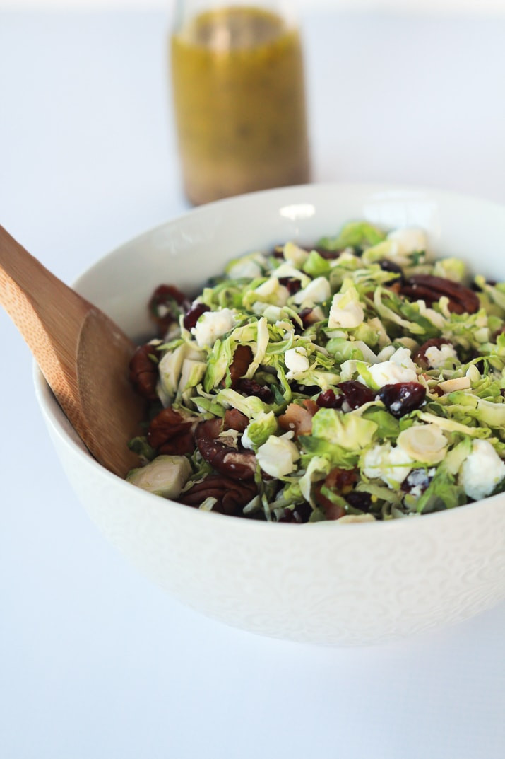 Nutritious Shaved Brussels Sprouts Harvest Salad filled with bacon, cranberries, and goat cheese then topped with a Hard Apple Cider Vinaigrette to spice things up!