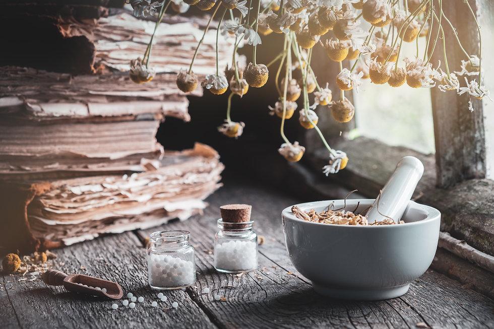 Mortar of dried healing herbs, bottles o