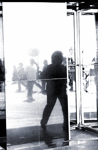 This reflection at a revolving door creates a tug of war between outside and inside space.