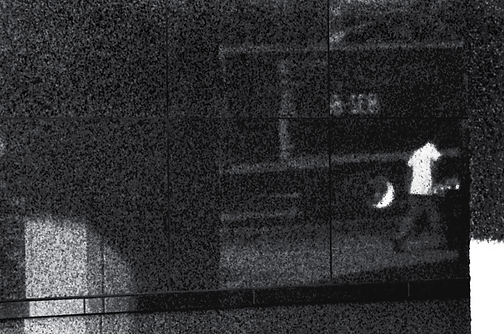 This reflection against a black granite buildind on 19th St in Washington, DC, depicts a worker making a Saturday morning delivery.