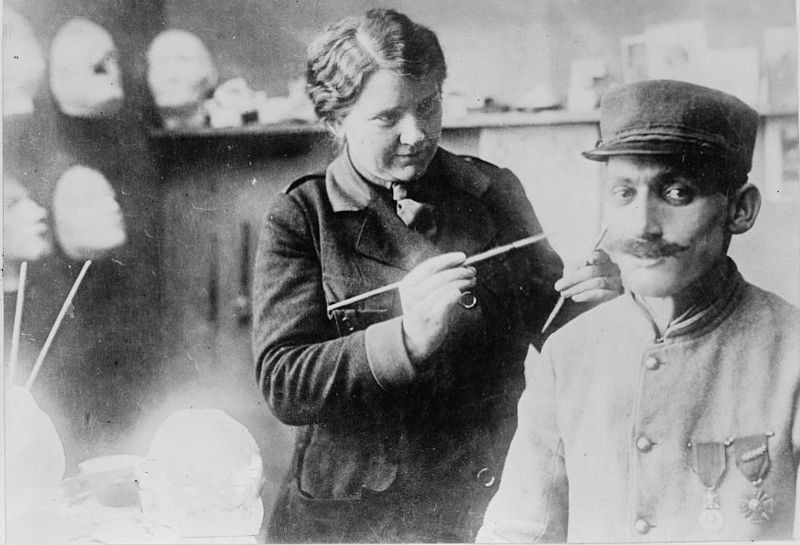 Ladd working on a mask with a soldier in her studio (1918)
