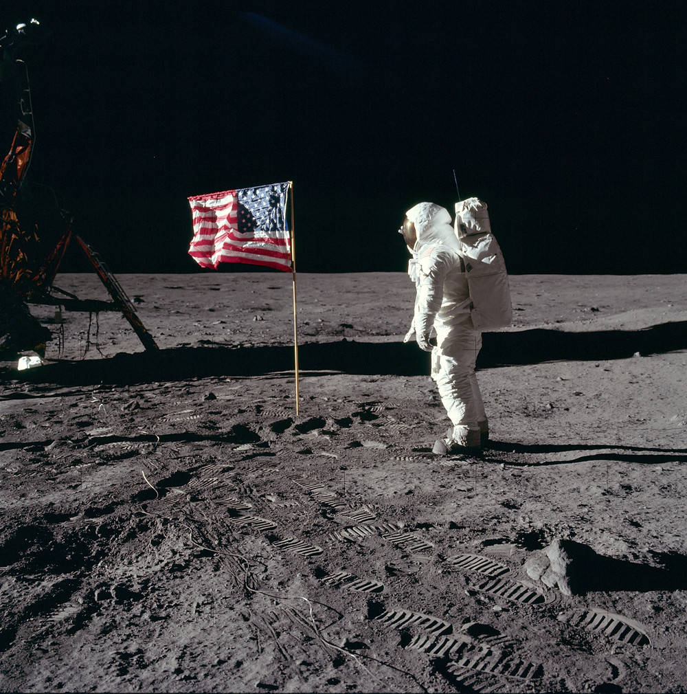 Making a Big Difference on a Small Planet: A conversation with Ellen Stofan, Director of the Smithsonian National Air and Space Museum | Buzz Aldrin salutes the U.S flag on the Moon (mission time: 110:10:33). His fingertips are visible on the far side of his faceplate. Note the well-defined footprints in the foreground. Buzz is facing up-Sun. There is a reflection of the Sun in his visor. At the bottom of Buzz's faceplate, note the white 'rim' which is slightly separated from his neckring. This 'rim' is the bottom of his gold visor, which he has pulled down. We can see the LEC straps hanging down inside of the ladder strut. In the foreground, we can see the foot-grabbing loops in the TV cable. The double crater under Neil's LM window is just beyond the LM shadow. | NASA / Neil A. Armstrong