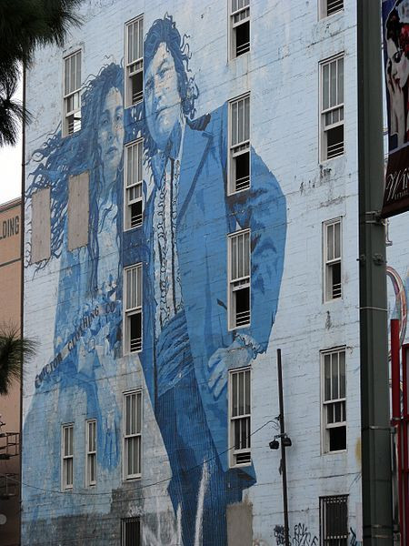 Transforming Communities with City Murals | Bride and Groom mural by Kent Twitchell. Mural in Los Angeles, California on the Victor Clothing Company by Claumoho via Wiki Commons