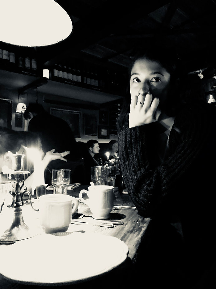 A young girl sits at a restaurant table with her chin in her hand