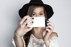 Girl taking selfie with phone, studio sh