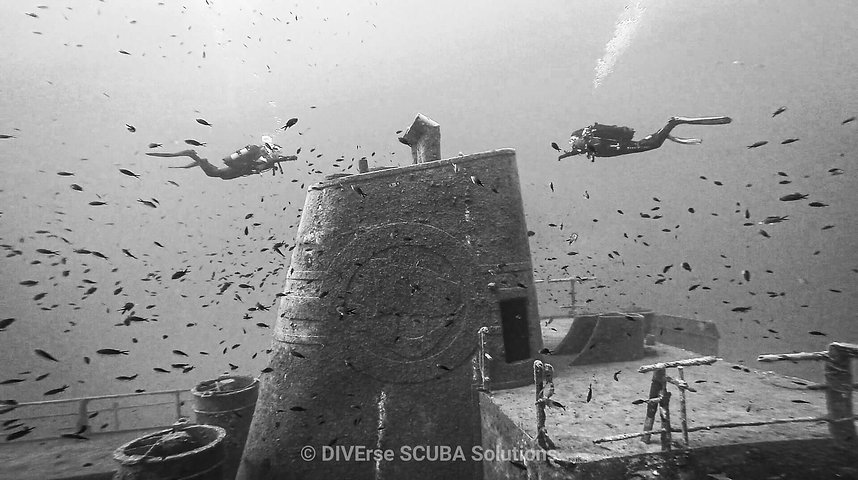 Divers facing each other on a wreck