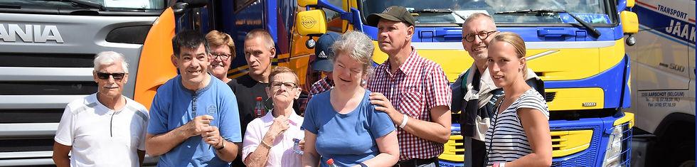 Een groep bewoners met een beperking staat lachend bij elkaar