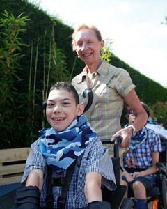 Vrijwilliger Mia duwt de rolstoel van een jonge bewoner met een beperking