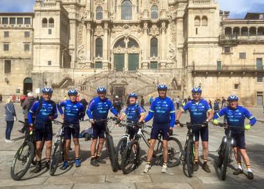 7 leden van mountainbikegroep het Calluna Team staan met fiets en in wielerstenue op het plein in Santiago de Compostella