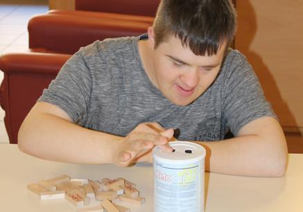 Een bewoner is geconcentreerd bezig aan een activiteit met blokjes