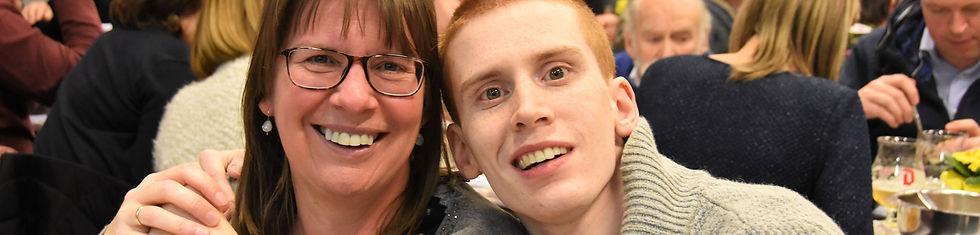 Een jongeman met een beperking omarmt lachend een medewerker van Ter Heide