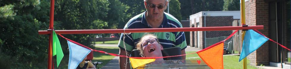 Bewoner van de dagopvang geniet van een rolstoelparcours samen met haar vrijwilliger