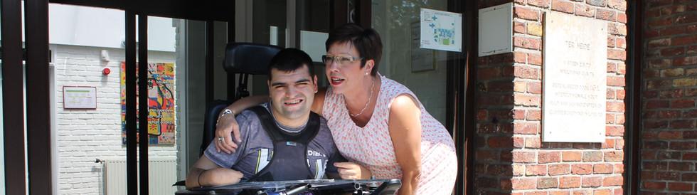Medewerker slaat arm rond bewoner in rolstoel
