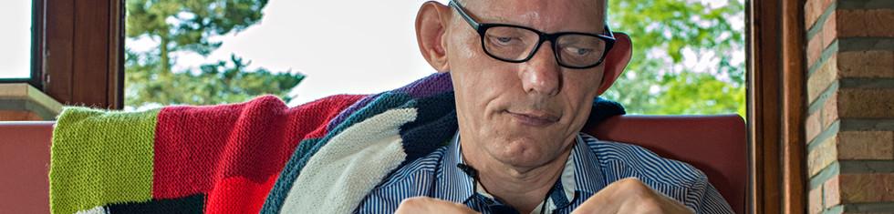 Een man met een beperking haakt kleurrijke sjaals en dekens