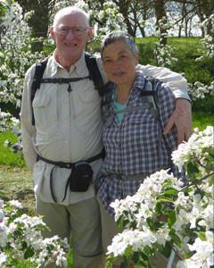 Vrijwilligers Guy en diane staan te midden van de bloesems lachend naast elkaar