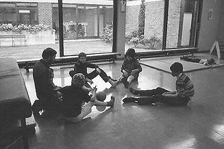 In een zwart-witfoto zitten enkele bewoners samen met een begeleider in een kring op de grond