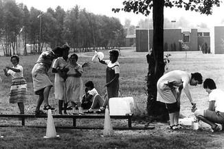 Op een oude zwart-witfoto spelen enkele bewoners en medewerkers buiten