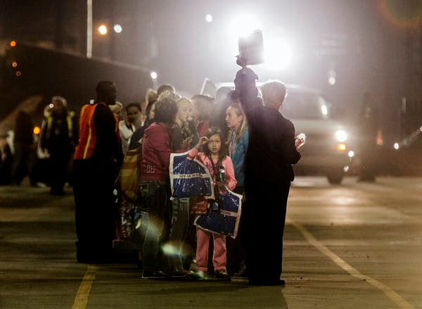 Passengers wait to board a bus after disembarking from the Carnival Triumph