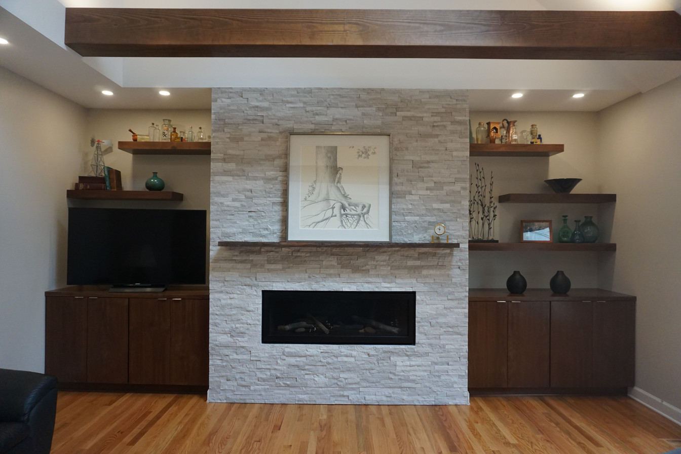 After stacked stone fireplace surround accentuates this gas fireplace and floating live edge mantel.