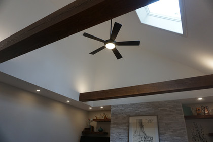 Wrapped beams are stained to match the walnut built ins and draw the eye upward.
