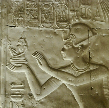 The King Seti I offering Maát (order, harmony) to the gods Osiris, Isis and Horus; from inside the Seti I temple.