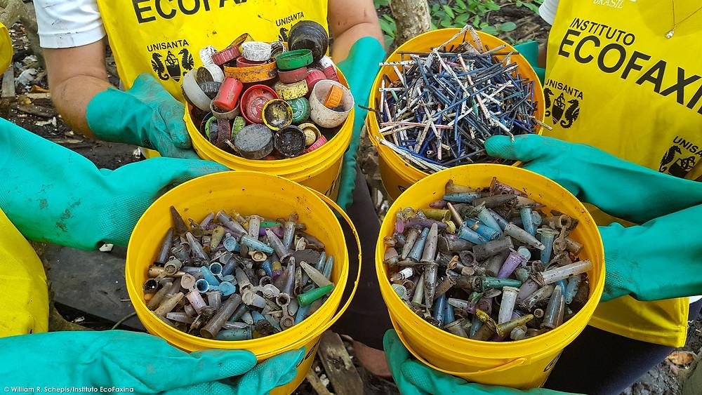 Voluntários exibem resíduos coletados no manguezal