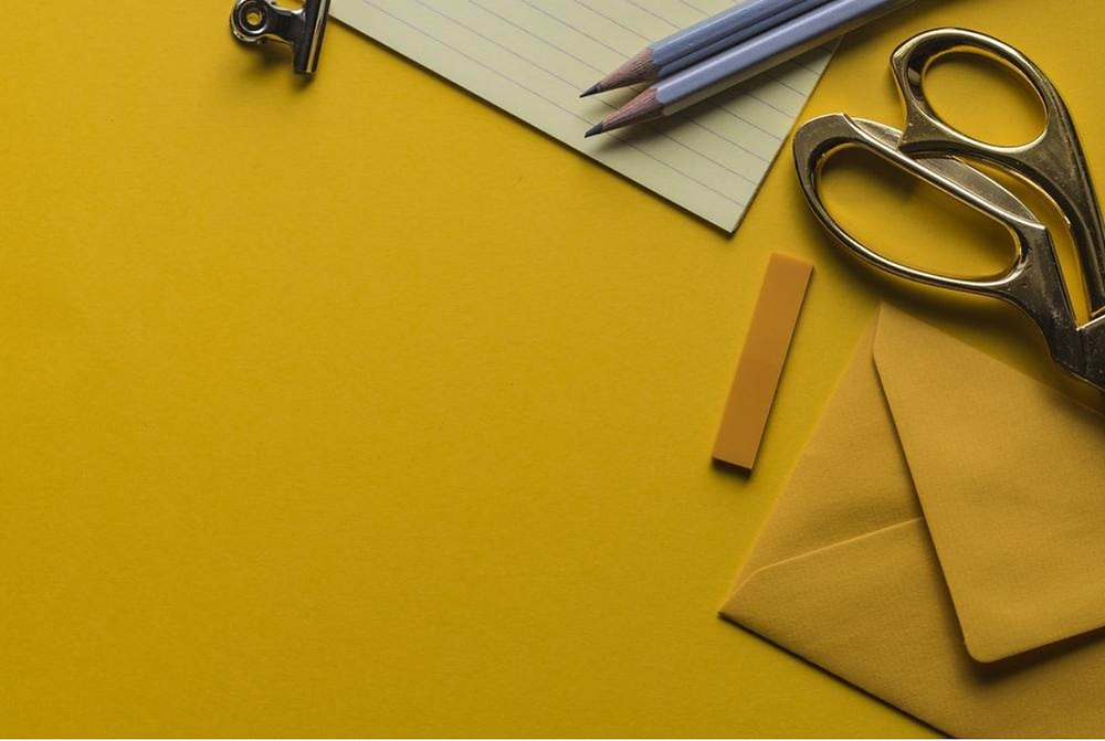 Workshop with scissors, envelope, pencils and a notepad on a yellow background