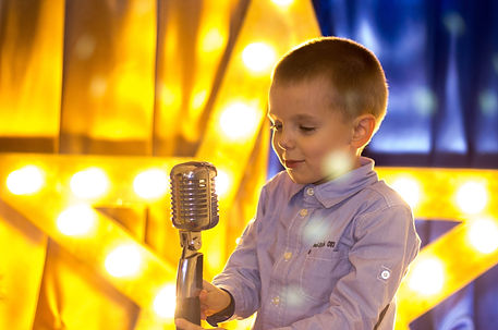 Young talent boy singing with retro micr