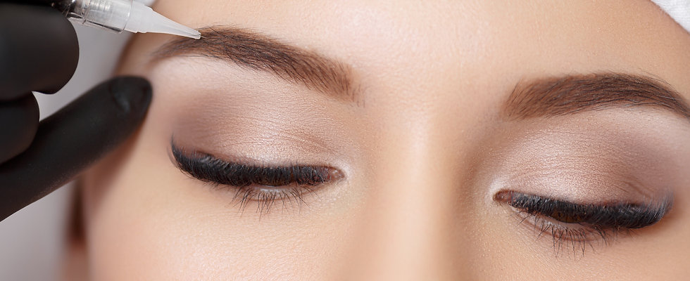 Close up of beautiful closed eyes and eyebrows and hand holding Microblading tool