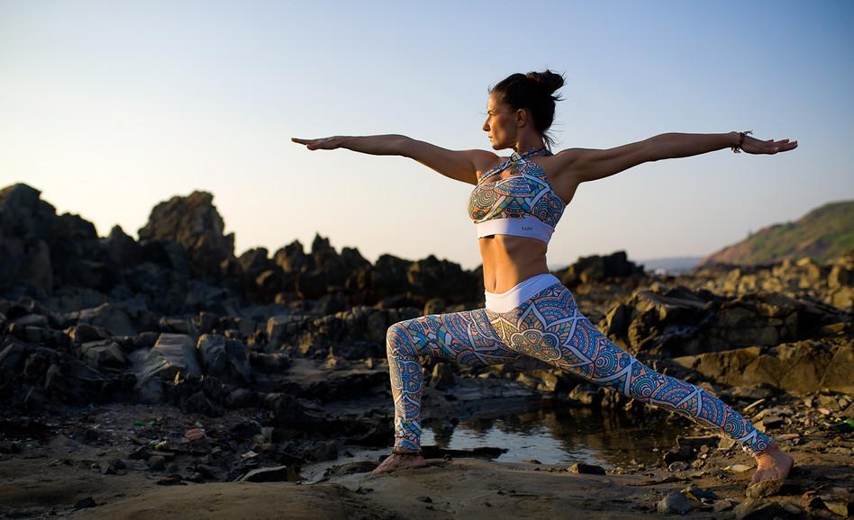 photo of a yoga asana on a rocky beach