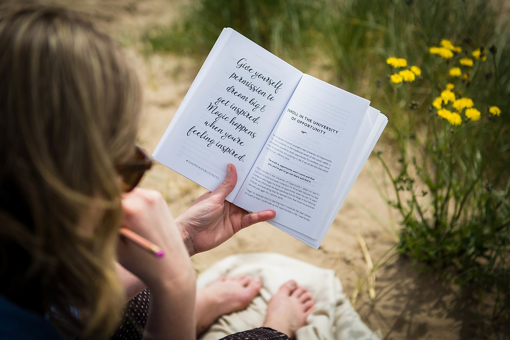 Siobhan reading inspirational books at the beach