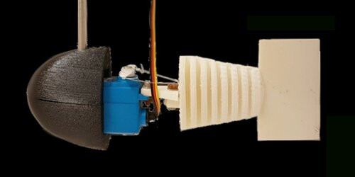 The researchers' simple robotic unit. The white material is 3D printed using deformable polymers. A servomotor (blue) drives two cables which provides the deformation of the robot. The dark part is 3D printed in a solid material. Credit: Sanchez-Rodriguez et al.