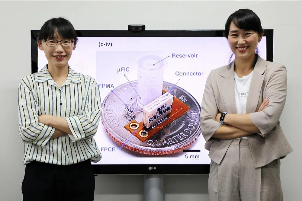 Prof. Sohee Kim and Dr. Yoo Na Kang from the Department of Robotics Engineering at DGIST standing in front of an image of their flexible neural interface. Credit: DGIST